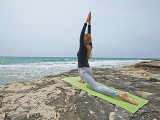 Healthy woman doing Joga by the Sea