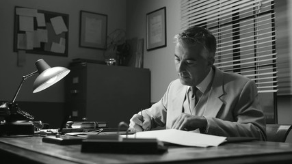 Confident vintage businessman working at office desk and signing