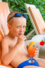 cheerful boy drinks juice at resort
