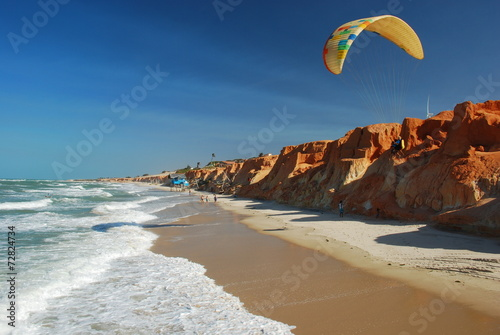 Plexiglas Luchtsport parapentiste volant entre plage et falaise