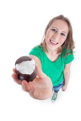 Junge Frau zeigt angebissenen Schokokuss und lächelt