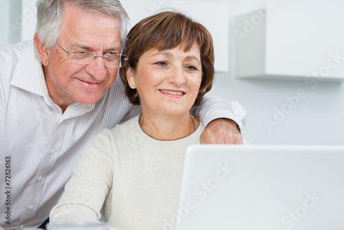 Seniors couple using a laptop computer - 72826163