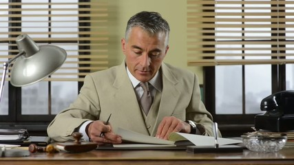 Confident vintage businessman working at office desk and checkin
