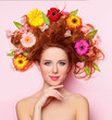 Beautiful redhead girl with flowers on pink background