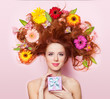 Beautiful redhead girl with flowers and gift on pink background