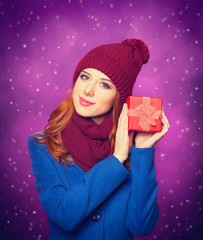 Redhead girl with gift on violet background.