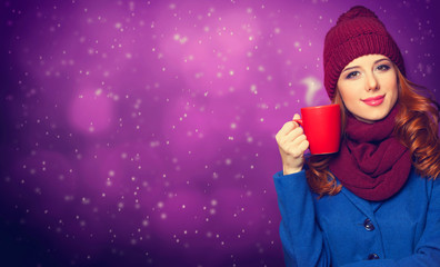 Smiling redhead girl with cup on violet background.