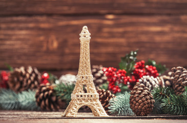 Eiffel tower toy with pine branches on a table.