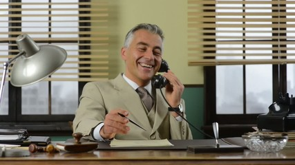 Confident vintage businessman working at office desk and talking