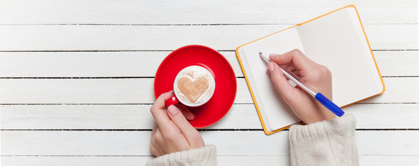 Female hand writing something in notebook near cup of coffee.