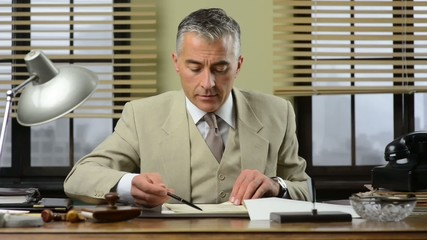 Confident manager working at office desk checking paperwork.
