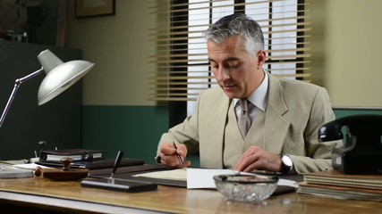 Confident manager working at office desk checking paperwork and