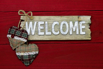Welcome sign with Christmas hearts on red wooden background