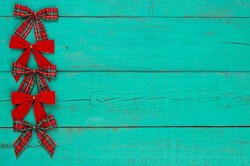 Red Christmas bows border antique green wood background