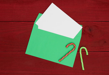 Christmas card, letter, candy canes, red wooden background