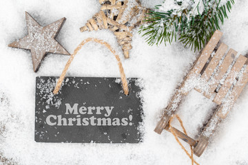 Christmas decoration over snow, wooden background