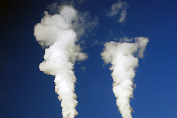 Two streams of steam in the blue sky.
