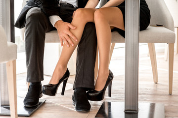 Legs of a couple sitting at the restaurant