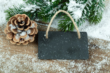 Black board of slate on old rustic wooden background, with snow