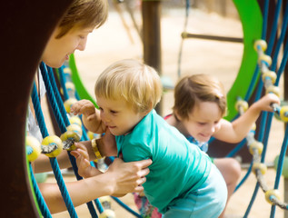 little sisters with mother at  playground