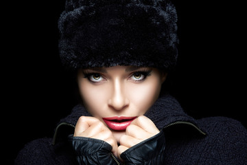 Winter Fashion. Beautiful Young Woman in Fur Hat and Mittens