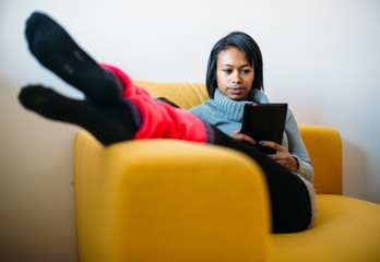 Young woman reading ebook on couch