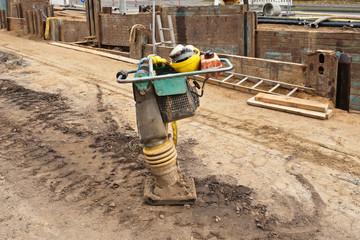 Arbeitshandschuhe und Schutzhelm liegen auf einem Sandstampfer