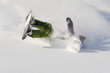 Snowboarder falls on fresh snow