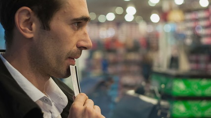A young man with a credit card hesitate in buying at the