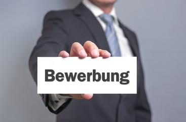 Businessmann hält Bewerbungs-Schild