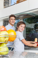 father and son smile cooking home kitchen