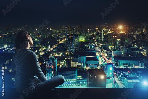 Leinwandbild Motiv Pensive woman is looking at night city