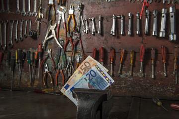 Officina con morsa e soldi