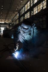 Welder welding in a workshop.