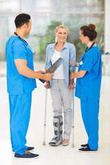 healthcare workers with injured woman on crutches