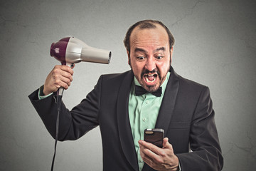 angry man screaming looking on smartphone holding hairdryer