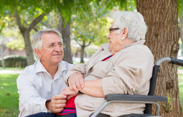 Man and senior woman in wheel chair talking at the park