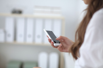 Businesswoman sending message with smartphone sitting in the