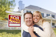 Couple in Front of New House and Sold Sign