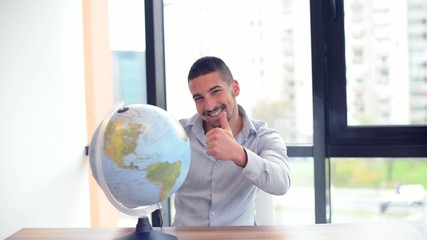 Young businessman with globe smiling