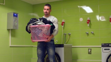 Young man holding basket of dirty laundry