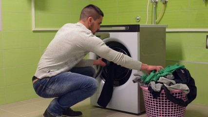 Young man putting dirty laundry to washing machine
