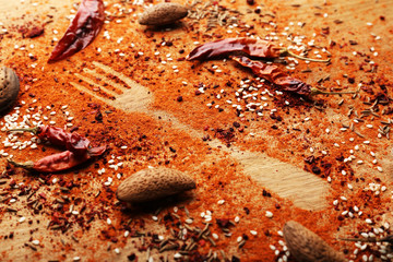 Spices on table with fork silhouette, close-up
