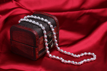 Silver necklace on red silk background
