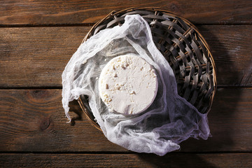 Cottage cheese on gauze on wicker mat on wooden background