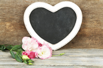 Beautiful eustoma flower and chalk board on wooden background