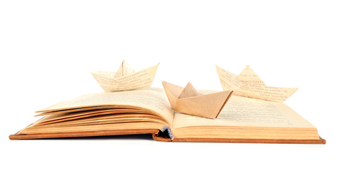 Origami boat on old book, isolated on white
