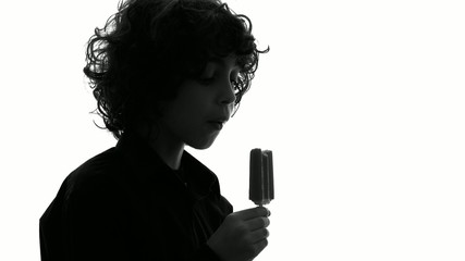 Silhouette of young child eating a popsicle