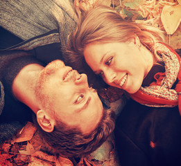 Happy loving couple lying on autumn leaves , close-up