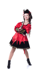 Bold young girl posing in pirate costume with gun